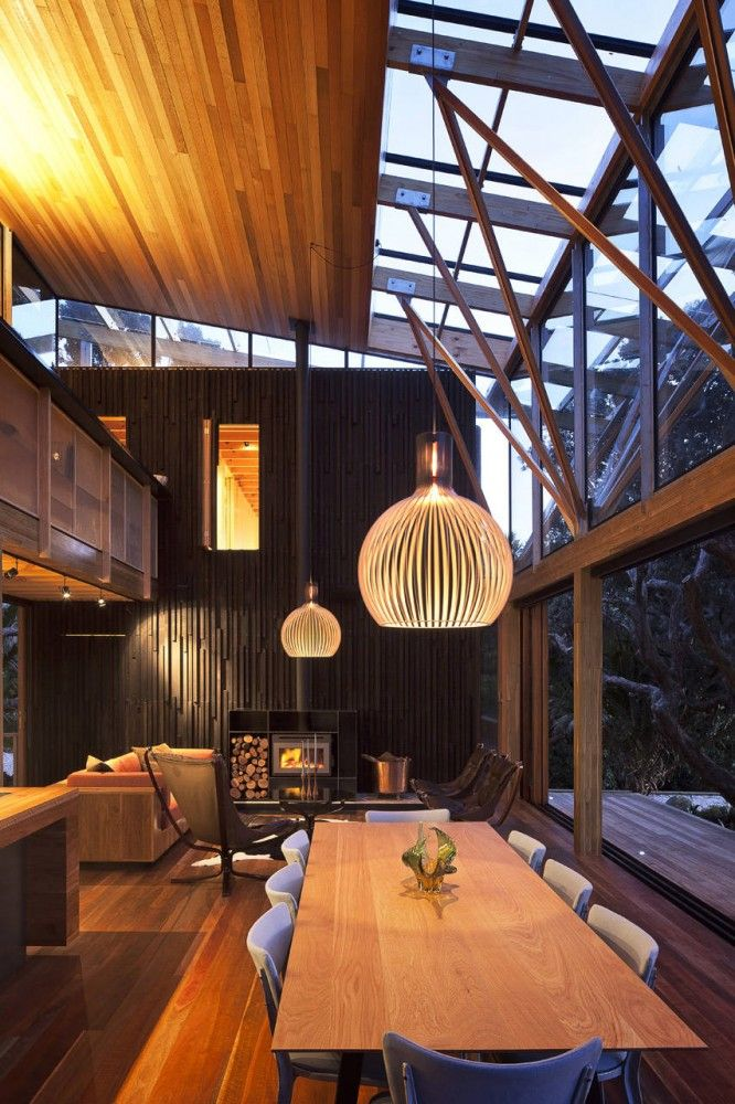 Under Pohutukawa Residence #dining_room in Piha North, New Zealand / Herbst Architects #skylight #wood_ceiling #contemporary #fireplace