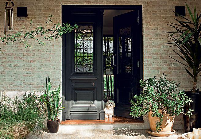 De estilo inglês, a porta comprada em uma loja de de demolição e recebeu pintura automotiva preta, para contrastar com as paredes de tijolos à vista e esbranquiçados
