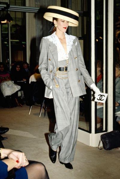 Modevisning. Modell i grå kostym med gulddetaljer, spetsblus och hatt. Från Chanel.