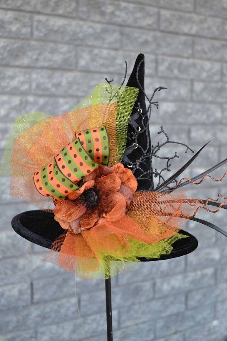 Waltz around town in this chic mini witch hat with orange and green accents. It is designed to sit stylishly askew on your head and ties under your chin. Black Velvet (ties) 10 inch brim; 9 inch tall
