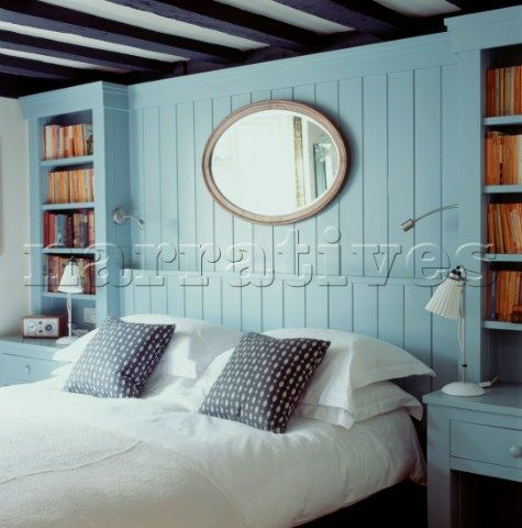 Bedroom with double bed and crisp white bed linen The pale blue tongue and groove bedhead is built i