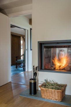 Double-sided fireplace with pull-down glass doors by Roderick James Architects