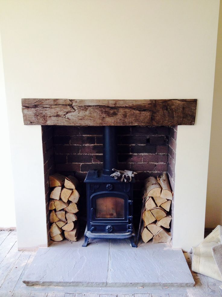 Log burner. Wooden lintel. Brick fireplace.