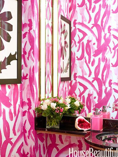 """Nisbet upholstered the powder room walls in one of her own fabrics, custom-colored in """"hot, hot, hot pink."""""""