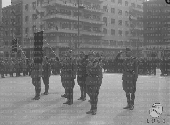 Volontari coi gonfaloni dei Battaglioni della G.I.L. e ufficiali schierati al centro di una piazza delimitata da militari e volontari schierati  RG/RG126/RG00005869.JPG