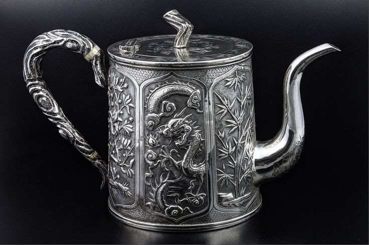 Lot 579, An early 20th Century Chinese silver repousse oval tea pot with panels of flowers, dragons, bamboo and carp, with an armorial panel and ivory resistors, 466g, sold for £1,100