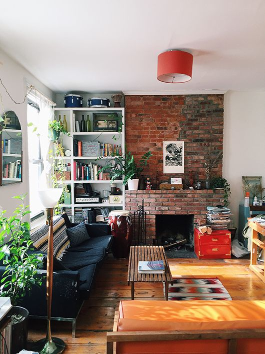An eclectic mix of furnishings. Love the bookcase set into the brick
