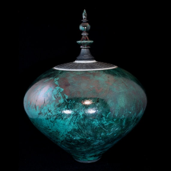 This glorious vessel fired in a coppery green Raku has an added slip-trailed texture around the top of the pot. It also has an elegant spire lid that sets into the top. By Shane Porter. Just love these colors and I sure miss my wheel!