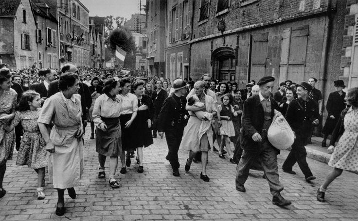 18. August 1944, Chartres, Frankreich: Eine französische Frau, zum Zeichen der Schande kahlgeschoren, wird durch die Straßen getrieben. Im Arm hält sie ihr Kind von einem deutschen Soldaten. © Robert Capa/Magnum Photos/Agentur Focus