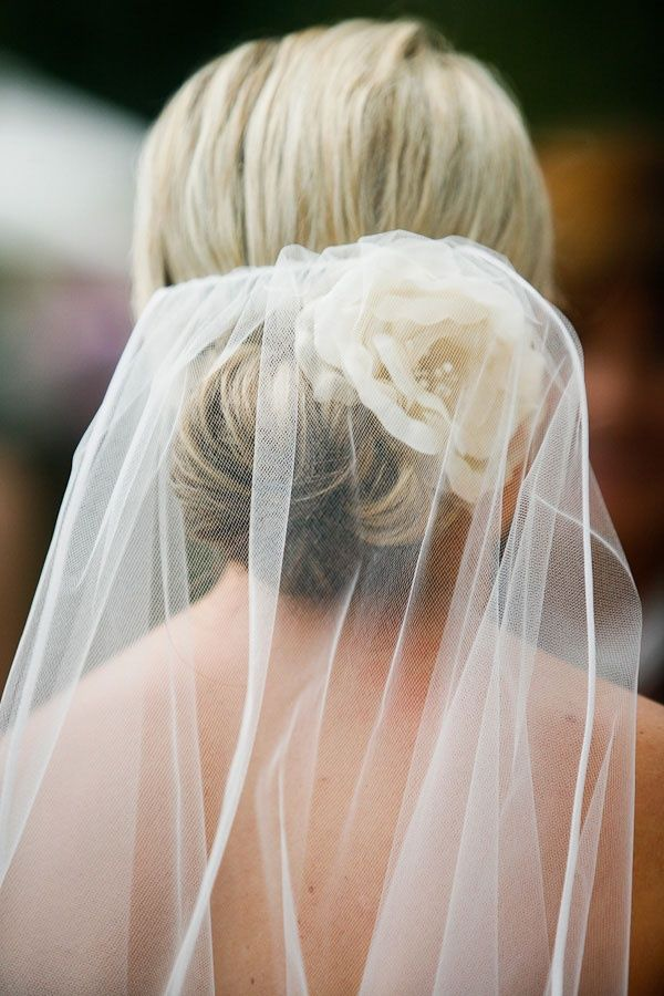 low nape bun, with veil. instead of the flower, maybe a hairpin