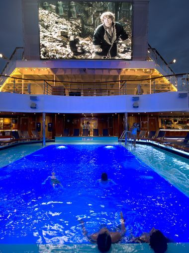 "Youngsters on the Carnival Freedom watch a ""Dive in Movie"" on the Lido Deck's Seaside Theater from the pool."