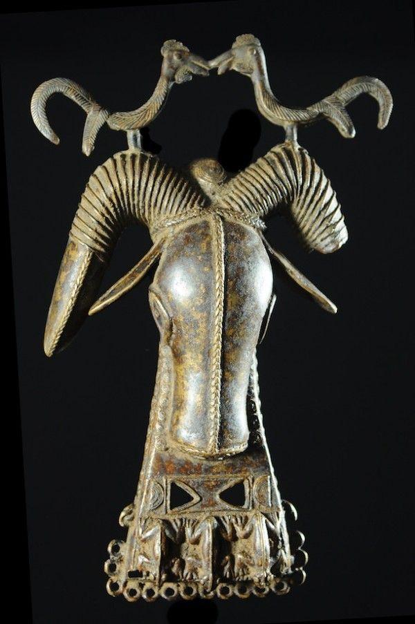 Voici un splendide médaillon en bronze, production typique du savoir-faire des bronziers de Bénin City au Nigéria, très probablement XIX ème voire XVII siècle... Cette pièce représente le Bélier, animal royal par excellence, avec le léopard. Ces masques pendentifs étaient généralement portés sur la hanche gauche des officiers militaires. Les anneaux métalliques qui bordent la pièce servaient à l'ancrage de chainettes en métal auxquelles était attachés des grelots. On notera également ...