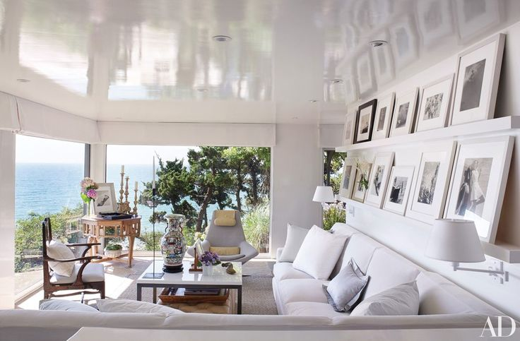 At the Long Island home of designers Vicente Wolf and Matthew Yee, framed photographs from Wolf's collection—including images by Louise Dahl-Wolfe, Edward Steichen, and André Kertész—line the shelves above the living room's sectional sofa, which is upholstered in a Janus et Cie fabric.