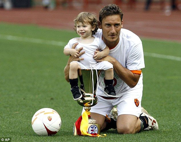 Totti poses for photographers with his son Cristian and the Italian Cup trophy in 2007