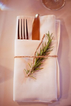 To cut costs on linens, we used a company's napkins, but folded them ourselves. To make them classy and stick with my wedding theme, we tied them with a piece of twine and stuffed them with a sprig of fresh rosemary that we cut from my mother-in-law's garden! (with her permission)