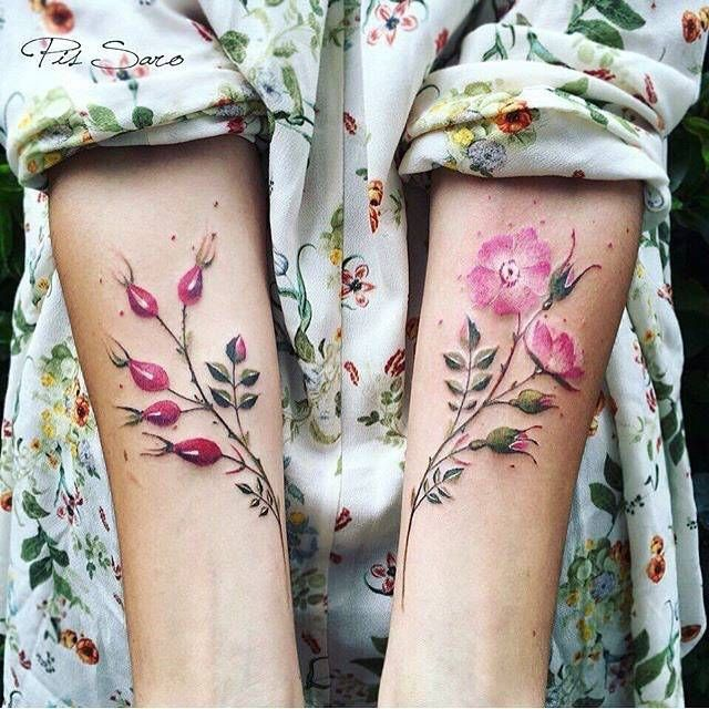 Matching flower tattoos on the forearm.