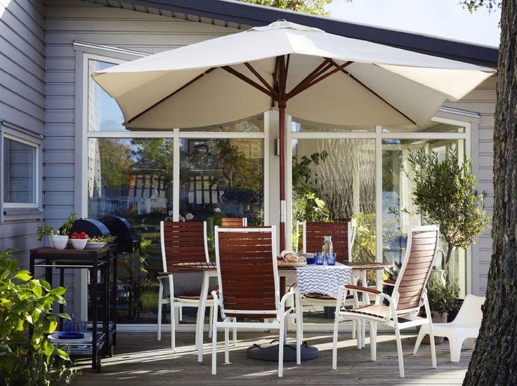 Eine große Terrasse u. a. mit VINDALSÖ Tisch und VINDALSÖ Hochlehnern für draußen weiß/braun lasiert und einem großen Sonnenschirm