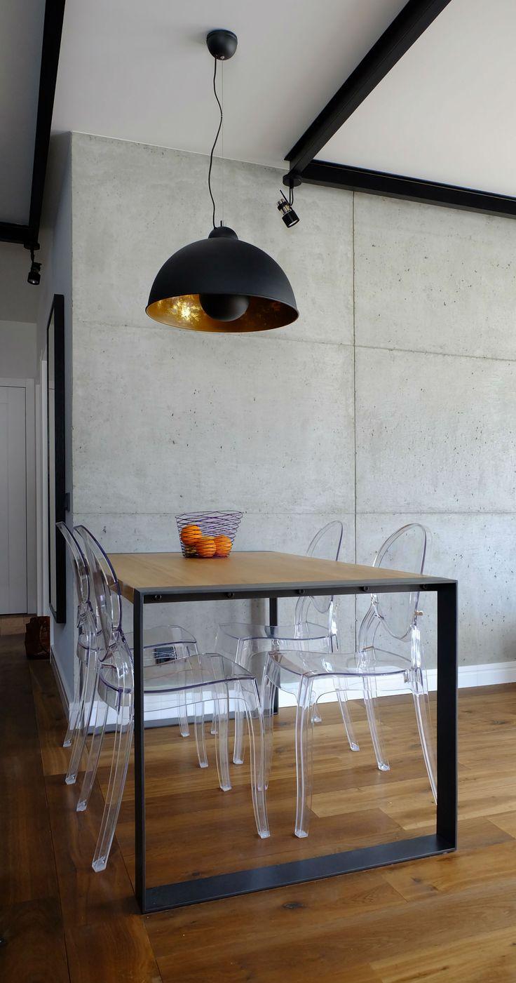Salon z betonową ścianą. Idustraialny stół. Nad nim stalowa lampa. Dębowy parkiet olejowany. Krzesła Victoria Ghost - P. Starck. Lampa