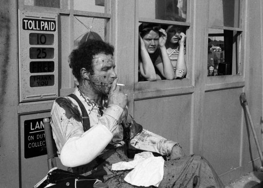 "James Caan takes a break during filming of the tollbooth assassination scene in which his character, Sonny Corleone, is blasted to smithereens in ""The Godfather."""