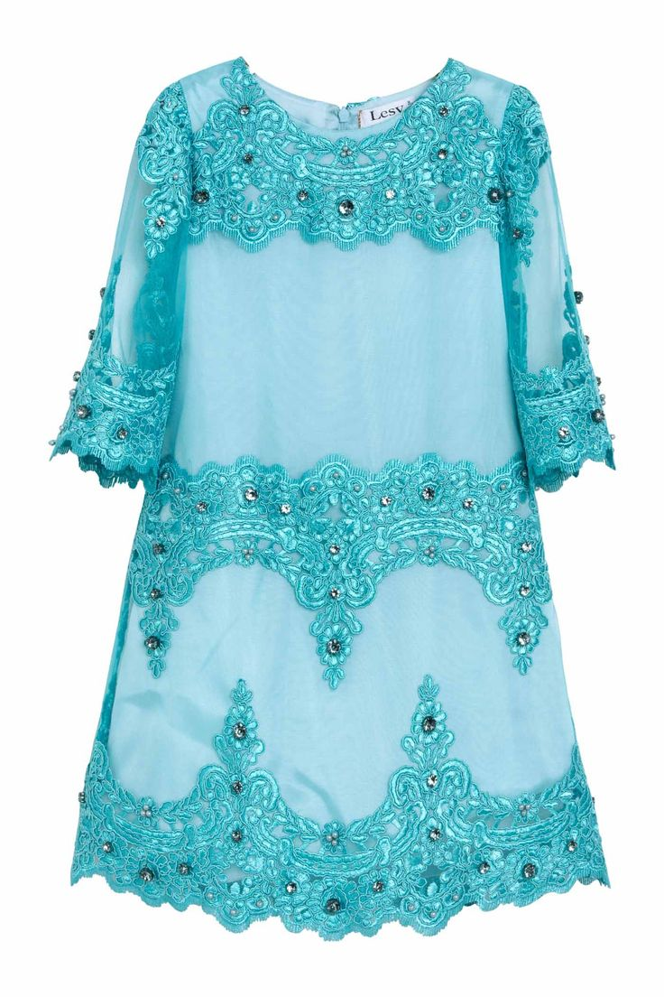 Luxury dress in beautiful turquoise tulle embroidered with an ornate floral design. The A-line dress has 3/4 length scalloped sleeves, round neckline and scalloped hem. The whole dress is embellished with sparkling turquoise stones hand sewn one by one.DELIVERY 7/14 DAYS