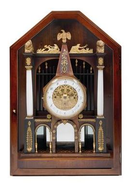 "An Empire commode clock from Vienna, Marked ""Peter Rau in Wien""; with obelisk, decorated with marquetry, triple mirrored, alabaster- and brass columns, gilt painted carved lion- and eagle finials, 52 cm, Austria ca. 1820."