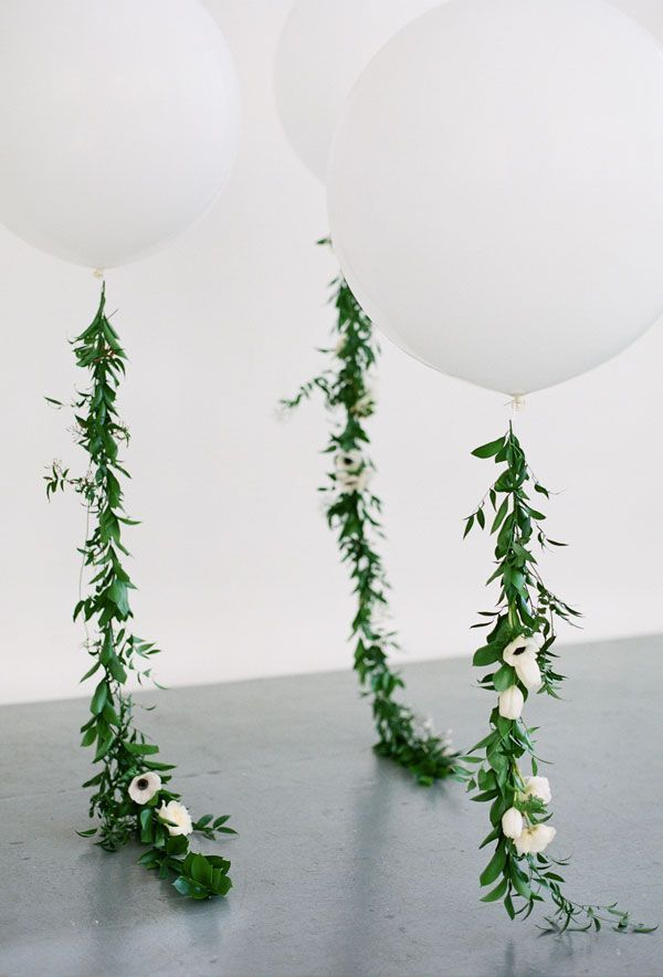 White Balloons. One per table. Instead of greenery, there would be white and green tissue paper tassels down the ribbon.