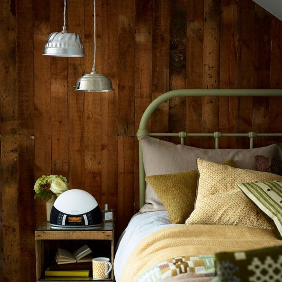 The wood-panelled wall in this bedroom gives a log cabin feel, while layers of tactile textiles add to the hunker-down vibe.