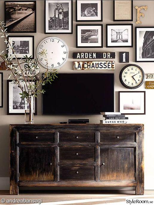 tavelvägg,tvbänk,tavlor,klocka,skyltar,vas,kvistar,vardagsrum. TAvelvägg runt tv