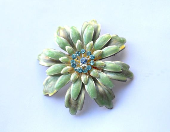 Spring is springing with this blooming brooch!  An impressively beautiful vintage flower brooch. There are three layers of petals in mint, celadon and turquoise colours, a circle of emerald rhinestones and sky blue one in the middle. The petals are made of light metal so its not too heavy.  It measures 6 cm (2.36) across.  This brooch is in a very good vintage condition and closes safely.  Just living is not enough. One must have a sunshine, freedom and a little flower. ~ Hans Christian…