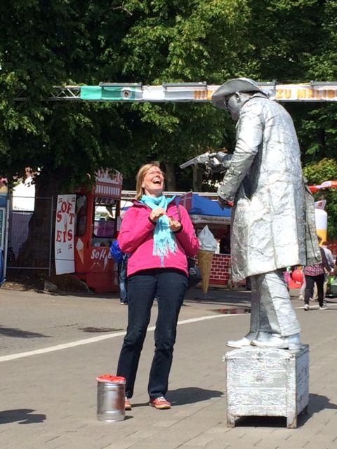 Nimmts mit Humor: Eine Passantin wird von einem Straßenkünstler bedroht.