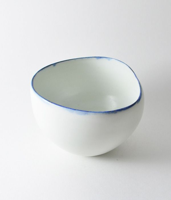 """Studio Joo. Made and designed Elaine Tian. Porcelain bowl, approx 3.5"""" wide, 3.5"""" high. wheel thrown, then hand-altered. White glaze, cobalt blue rim. Food/dishwasher/microwave safe. All items in this store are made in the wabi sabi tradition. Irregular textures and surfaces are part of the work. Sold out"""