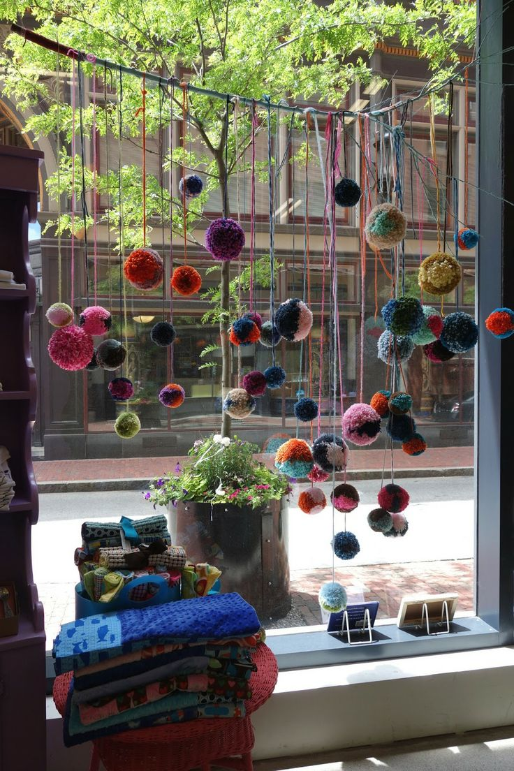 hanging branch with colorful pom poms for window display