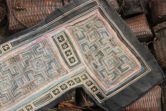 Vintage Hmong batik Fabric. The inspiration for these batik motifs are derived from the natural environment, and are made with the wax relief method with a natural indigo dye obtained from a flower grown on the edges of the rice terraces.  Fabric reclaimed from the tribal outfit of the Black Hmong . All cotton fabric, machine embroidery, hand stitched applique squares and of course the hand drawn batik. Would look great on the wall, or re-imagined into a cushion cover, pillow, bag....the…
