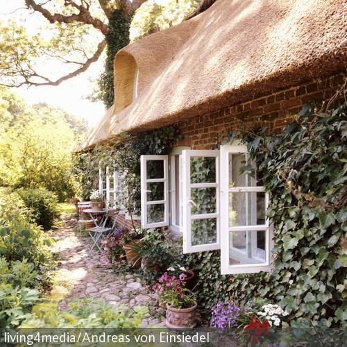 Duftende Blumen, Reetdach und mit Efeu umrankte Steinmauern – das ist Country Look pur! Die weiß gestrichenen Fensterläden versprühen zusätzlich noch einen …