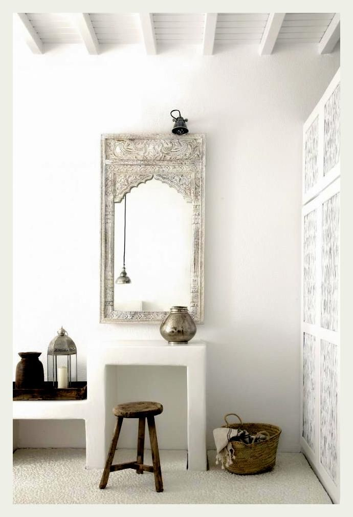 A carved wood Indian mirror, white on white.