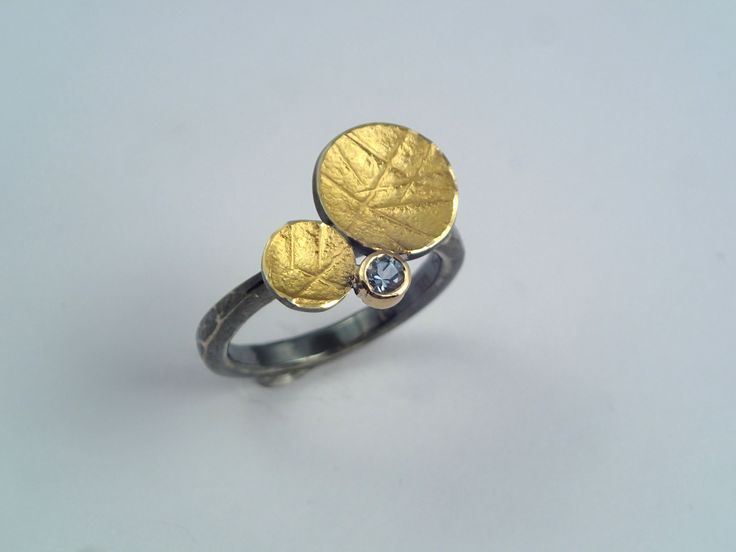 A different gold and patina silver ring with circles and an aquamarine stone.