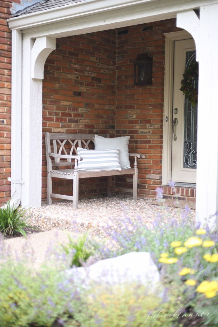 Simple pebble porch with copper lanterns, a weathered bench and soft green pillows