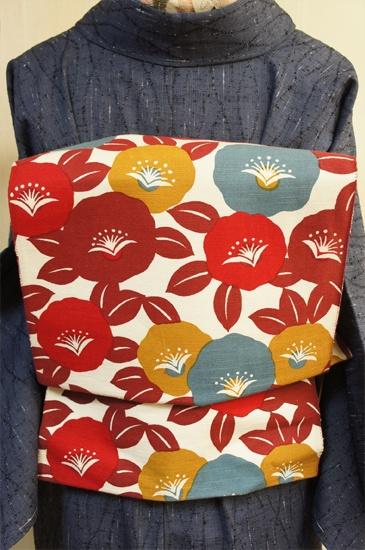生成り色とブラウンをベースに、からし色やウイスタリアグレー、スカーレッドが差し入れられたニュアンス感のある色選びも印象的に、レトロモダン椿模様が染め出された綿紬風つくり帯です。