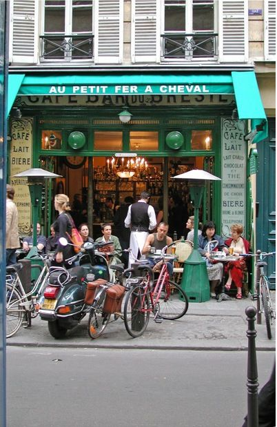 Le Petit Fer a Cheval  Rue Vieille du Temple, in the Marais  As you should know by now, the Marais area is as well-roundedly trendy as you're going to get in Paris. So where else better to people watch than on it's most buzzing street? Le Petit Fer a Cheval is a charming century-old Parisian brasserie with a unique horse shoe-shaped bar. It feels like nothing has changed in its decor since the 1920s and it's as cute as a button and about as small as a button too.