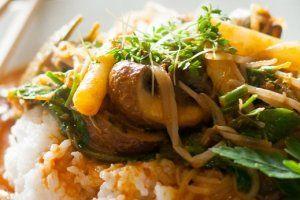 De heerlijke Thaise curry, rood van kleur, opgediend met basmati rijst, asperges, champignons en platte peterselie
