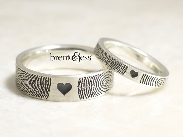 It's like you both just touched the ends of your fingers on the ring, each leaving your mark. Featuring a heart in between your two fingerprint prints. With our newest technology we carve your fingerprints into flat sterling silver bands with handcrafted comfort fit interiors. The finished widths are approximately 3mm and 6mm. We darken the fingerprints for contrast, but we can leave them in their subtle natural states if you'd prefer.  Made exclusively for you with your unique finger...