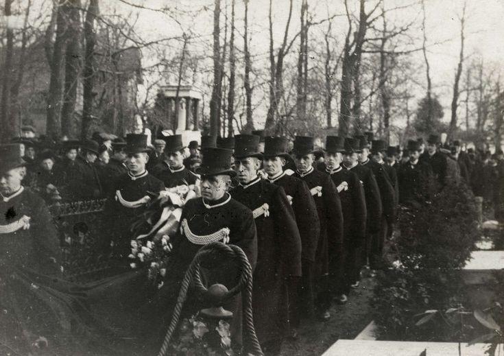 Begrafenis. Dragers mert tressen op hun uniform en met hoge hoeden begeleiden een begrafenisstoet. Foto 1910.