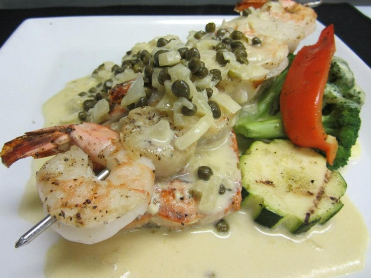 Cattlemen's Club Grilled wild salmon with tiger prawns and scallops poached in a caper cream   Visit us at 9380 Highway 97 North, Vernon BC or call us at (250) 542 - 2178.