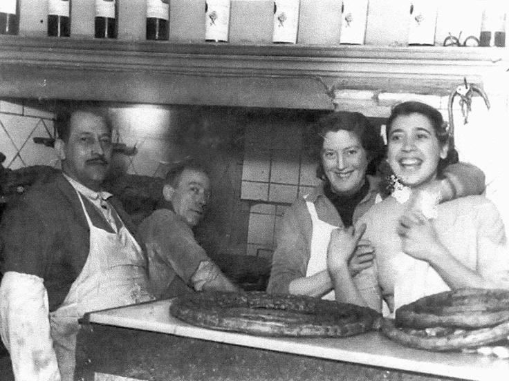 Interior de la Chocolatería La Esperanza€, donde se encuentra el dueño, Luis Pérez Peña, su oficial Sebastián, Pilar Peña y Pacita (una de las empleadas). Encima del mostrador, varias roscas€ de porras que se vendían a 30 pesetas. Las porras sueltas pequeñas (18 cm.) a 30 céntimos y las grandes (30 cm.) a una peseta. Foto de 1945 donada por Fernando Pérez Peña.
