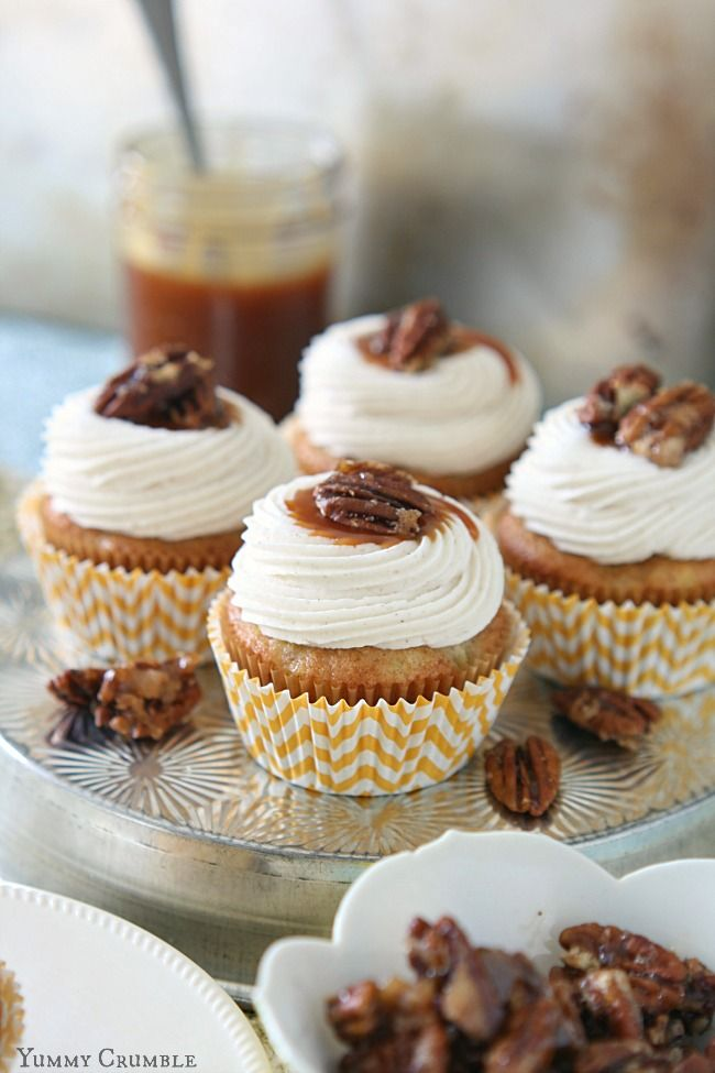 Salted Caramel Hummingbird Cupcakes with cinnamon cream cheese frosting, buttery salted caramel drizzled on top, and candied pecans.