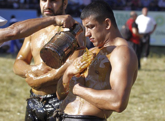 A participant rubs his body with oil during the 653th annual Kirkpinar oil wrestling tournament at the Sarayici arena in Edirne, northwestern Turkey, June 22, 2014. Wrestlers attend the annual Kirkpinar oil wrestling festival to compete in different categories during the three-day tournament in western Turkey, near the Turkish-Bulgarian border. (Photo by Osman Orsal/Reuters)