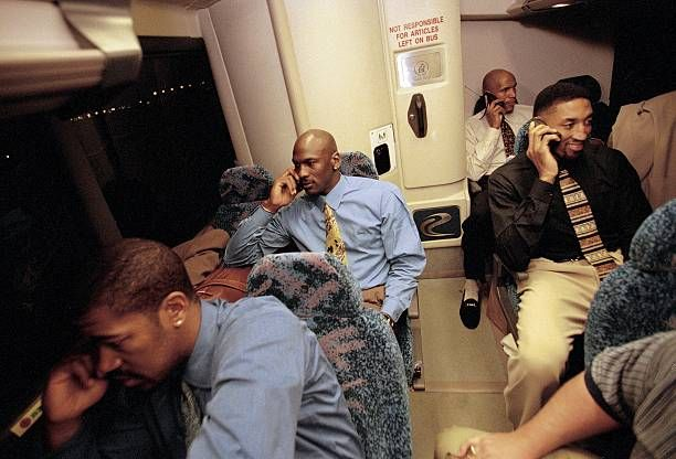 Basketball Portrait of Chicago Bulls Dickey Simpkins Michael Jordan Ron Harper and Scottie Pippen riding team bus and talking on cellular phones...