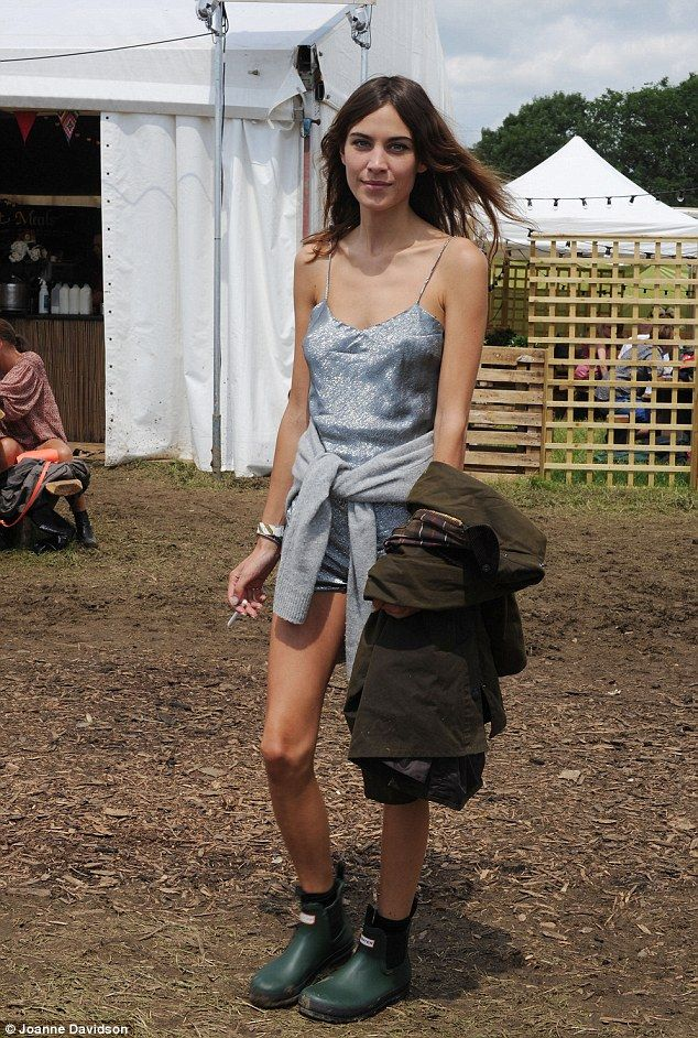 Alexa Chung (with her Barbour coat on her arm and Hunter boots) - At 2014 Glastonbury Music Festival.  (June 2014)