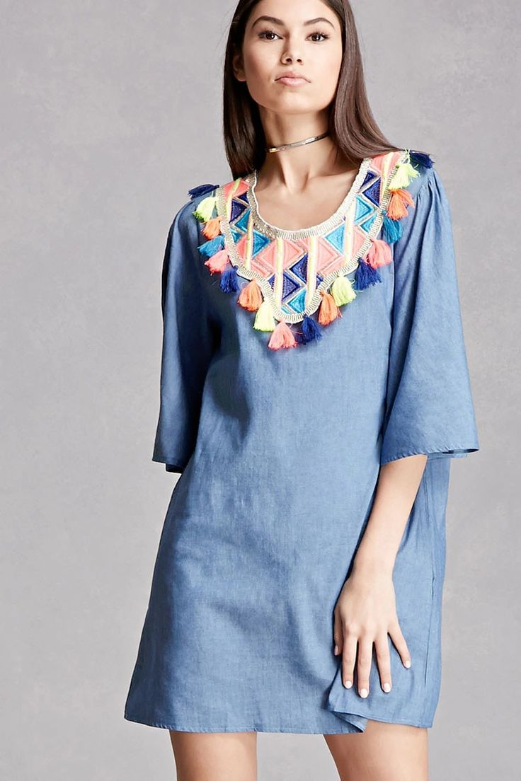 A chambray mini dress by Velzera™ featuring a colorful geo pattern embroidery, a tassel trim, round neckline, 3/4 bell sleeves, and a flared hem.