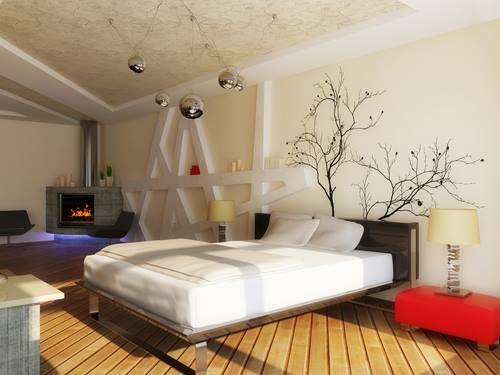 """""""Prostorná ložnice s krbem a sezením zjevně i s televizí. Samotné uspořádání prostoru je v pořádku. Zbytek však asi nepomůže ke klidnému spaní. Šikmé členění na zdi, stropě i podlaze prostor zneklidňují. Vystouplé prvky přidané různě na konstrukce jsou v krátkém úseku využitelné jako police, na stropě zcela postrádají smysl. Zařizovací prvky a dekorace by jistě samostatně působily vkusně, zde je jich však příliš. A ještě: proč teplé a romantické působení krbu ničit modrým podsvícením?"""""""
